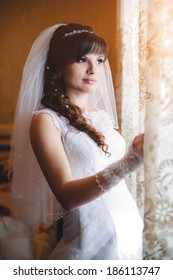 beautiful bride in white wedding dress with hairstyle and bright makeup. Happy sexy girl waiting for groom near the window. Romantic lady in bridal dress have final preparation for wedding