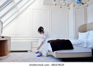 Beautiful bride in white wedding dress is wearing shoes. Beauty model girl in bridal gown for marriage is holding boots in her hands. Female portrait of cute lady indoors. Close-up woman's arms