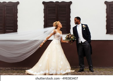 Beautiful bride woman in long elegant white lace dress veil and groom african American man just married couple hold bouquet on wedding day