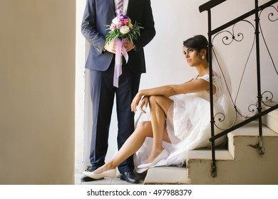 Beautiful bride woman with sexy legs in white wedding dress and veil sits on staircase near elegant groom man with bouquet