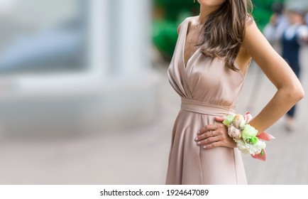 beautiful bridesmaid in a silk dress with a flower boutaniere on her hand against a green garden background