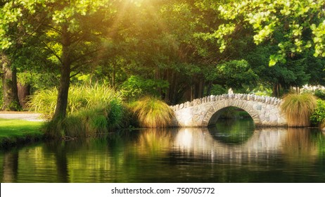Beautiful bridge in a botanical garden under warm sunlight in summer reflecting over pond water. Shot in a garden in Queenstown, New Zealand.