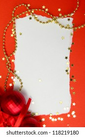 beautiful bright Christmas balls and empty postcard on red background