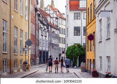Beautiful bright cityscape in perspective. View on cobbled street with bicycles. Narrow street with colorful buildings in old historic center of Copenhagen. Red tiled roofs. Four people men go forward