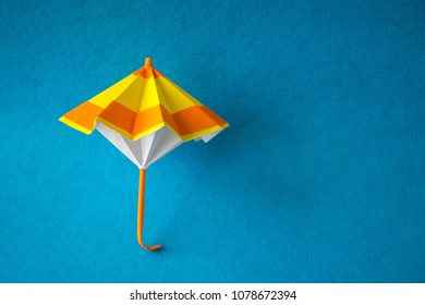 Beautiful bright colorful origami parasols. Creative handmade decoration design. Isolated on blue background. Copy space in right side