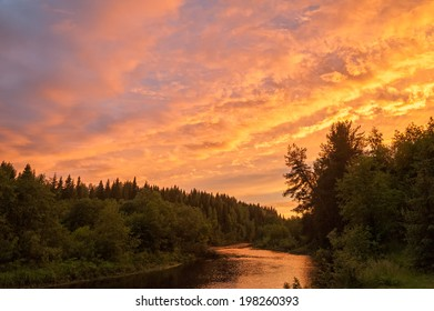 Beautiful bright dramatic sunset over river with forest along riverside. Arkhangelsky region, Russia.