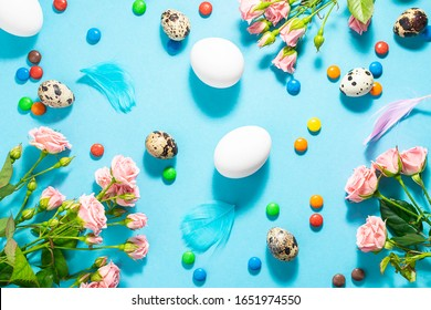 Beautiful bright Easter composition with eggs, flowers, candies and decorative feathers on blue background.