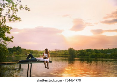 Beautiful bright fairy walk of a loving couple in the summer at sunset. A guy in a white shirt and jeans with a girl in a sarafan embraces, dancing, sitting on the pier. Pond in the background. Place