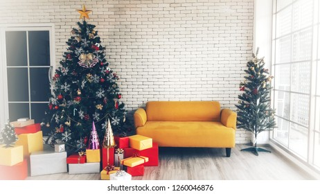 A beautiful bright living room decorated for Christmas eve with yellow sofa between Christmas tree and set of colorful box gifts , decoration toy lying on modern wooden floor background. Vintage style