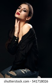 Beautiful bright makeup female model posing in black shirt with shoulder on dark shadow background and sexy touching herself neck