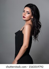 Beautiful bright makeup woman with long black curly hair style in black overalls dress, burgundy lipstick looking sexy on grey background. Closeup glamor portrait