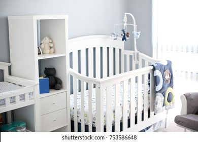 beautiful bright and modern baby room with a crib, mobile and stuffed toys