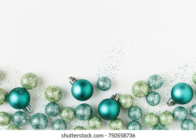 Beautiful, bright, modern Christmas holiday ornaments decorations in contemporary trendy blue and green colors with sparkling glitter on white background. Horizontal border banner image.