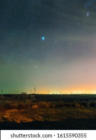 Beautiful bright night landscape. Winter cloudy starry sky over the rural scenery. Stars placers.