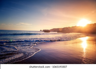 Beautiful bright purple purple sunset on the ocean, sandy beach, waves and glare of the sun