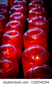 Beautiful bright red glass prayer candles lined up in rows.