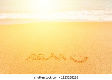 """Beautiful bright sandy beach by the blue sea. Inscription """"Relax :)"""" made on the sand"""