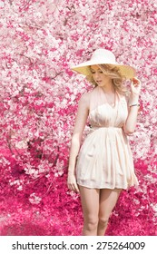 Beautiful bright smiling soft sweet girl with long blond curly hair wearing a hat with large fields in the summer pink sundress standing near a pink tree with white flowers