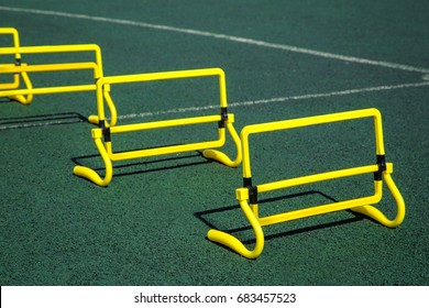 Beautiful bright sports gear for exercising and improving your health. Green turf at the stadium. Yellow small barriers to training children
