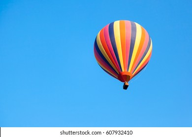 Beautiful bright striped balloon against the blue sky. Travel dream freedom concept