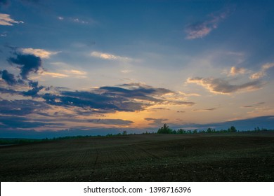 Beautiful bright sunset over a large plowed field in the spring evening.
