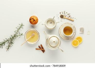 Schöner heller Teeservice. Weiße Teebeutel und Teezutaten auf dem weißen Tisch.