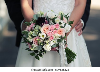 Beautiful bright wedding bouquet in hands of bride