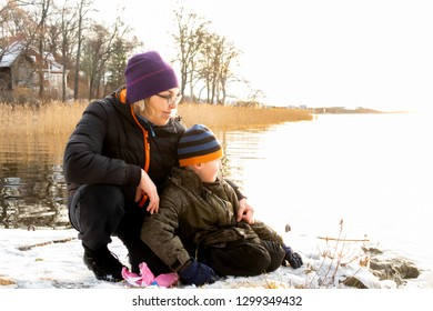 Beautiful bright winter landscape by the sea with a woman and child sitting in the snow on a rock looking over the water.
