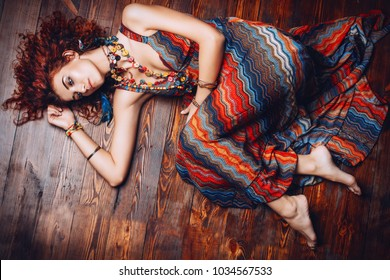 Beautiful bright woman with curly foxy hair lies on a wooden floor. Dress and accessories in boho style. Ethnic style in clothes.