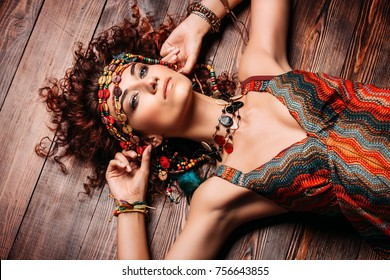 Beautiful bright woman with curly foxy hair wears a dress and beads in boho style. Ethnic style in clothes.