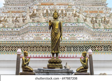 Beautiful bronze Buddha statue and statues of disciples at Wat Arun with patterned of white demon statue Thai architecture in the great pagoda at Wat Arun important famous temple in Bangkok Thailand.