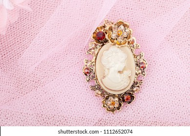 Beautiful brooch with cameo on a pink background