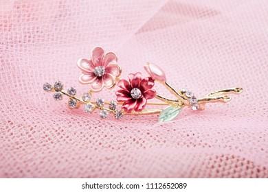 Beautiful brooch with flowers on a pink background