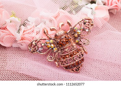 Beautiful brooch in the form of a bee on a pink background
