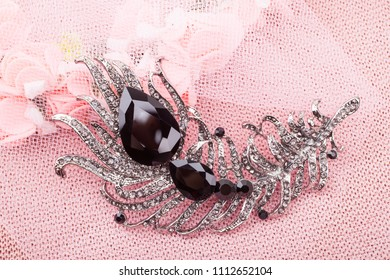 Beautiful brooch in the form of a black feather on a pink background