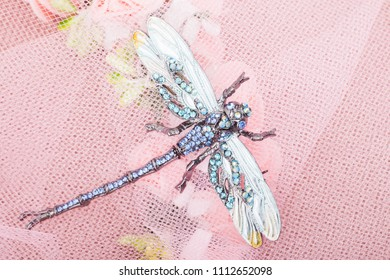 Beautiful brooch in the form of a dragonfly on a pink background