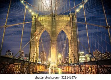 Beautiful Brooklyn Bridge in New York City seen at night from the pedestrian walkway