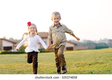 Beautiful brother and sister running and laughing together outdoors in a field with a suburban home in the background