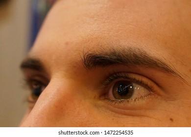 Beautiful brown eyes with dark eyebrow and long eyelash of French guy close up shoot