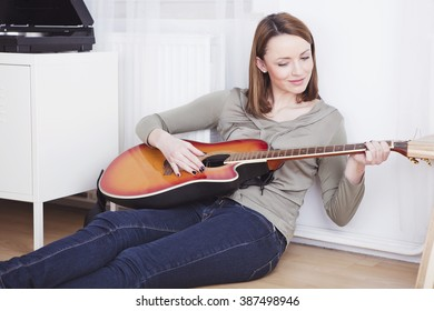 Beautiful brown haired girl casual dressed relaxing on the floor of living room while playing a song on guitar next to a record player