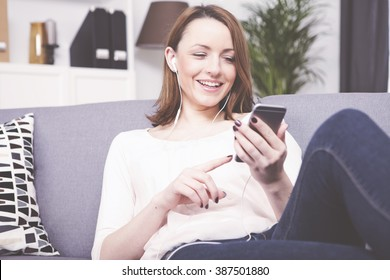 Beautiful brown haired girl sitting on sofa and listening to music with smartphones and earphones
