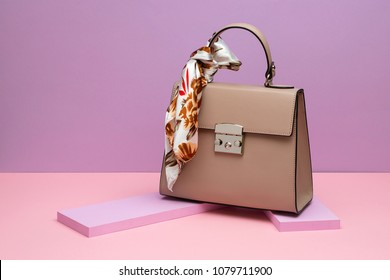 Beautiful brown leather female bag with a colorful silk scarf on the small pink boards on the peach surface on the violet background in the studio. Closeup. Horizontal.