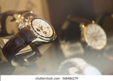 Beautiful brown leather watch in front of other watches. Focus on the watch.