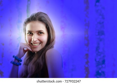Beautiful brown with long hair with smile looks at us, hand to mouth, blue background.