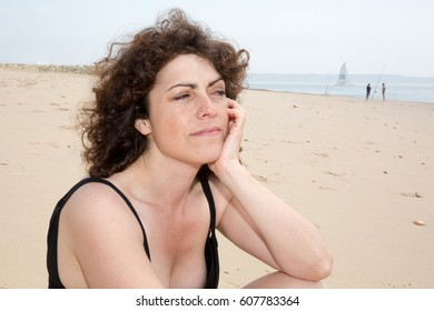Beautiful brown woman pensive on the beach beach during the holidays
