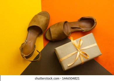 beautiful brown woman summer sundal and gift box isolated on orange background