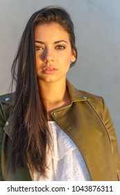 beautiful brown-eyed woman with urban style at sunset in the cit