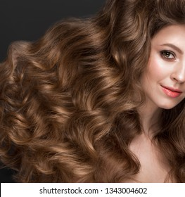 Beautiful brown-haired girl with a perfectly curls hair, and classic make-up. Beauty face and hair. Picture taken in the studio.