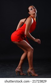 beautiful brunet woman in red clothes at black background