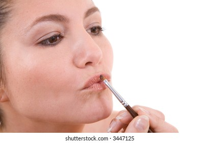 Beautiful brunette applying lipstick with pouted lips on white background